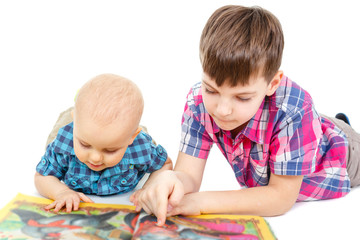 Two Smart children little baby boys in shirt reading a book on the floor, isolated on white background