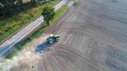 Aerial view on tractor ploughing field.