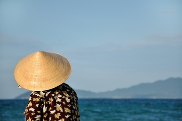 a woman with typical hat, observes the horizon at sea. Vietnam