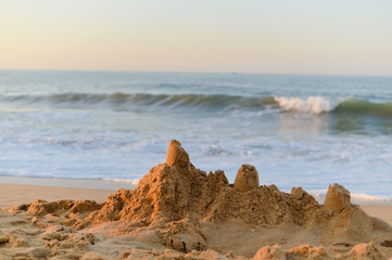 Sand castle on sunset beach sunny outdoors background