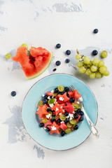 Fresh watermelon salad with feta cheese and berries on white stone table. Top view. Space for text