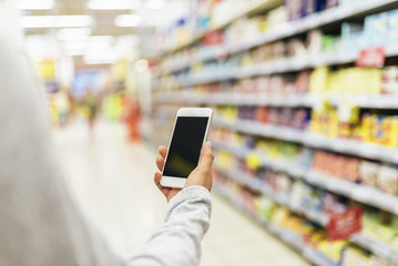 Close up of woman using her mobile in supermarket.