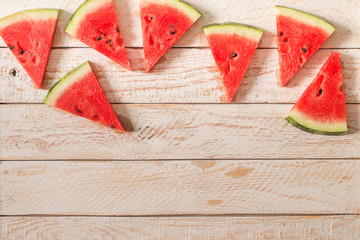 Slices of watermelon on wooden table.