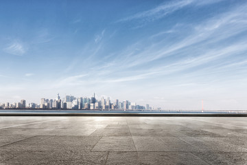 Fototapete - empty marble floor near water with cityscape of modern city