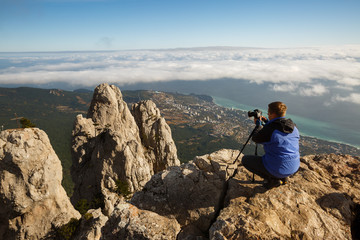 Man sitting with a tripod and photo camera on a high mountain peak above clouds, city and sea. Pro photographer adjusting dslr settings on rocky summit.