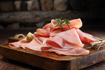 Sliced ham on wooden background. Fresh prosciutto.