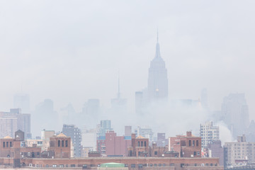 Wall Mural - New York City, United States of America - March 24: Misty Manhattan Dimond Reef skyline with Empire State Building and skyscrapers seen from Brooklyn Bridge on March 24, 2015.