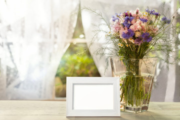 Empty white frame and vase with flowers