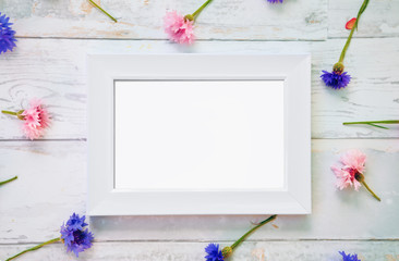 White frame mockup with flowers on table