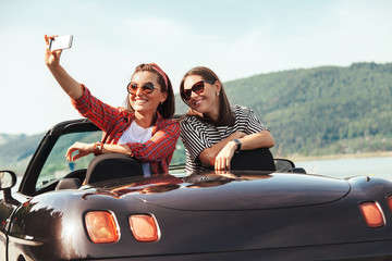 Two female freinds take selfie photo in cabriolet car with beautiful mountain lake view