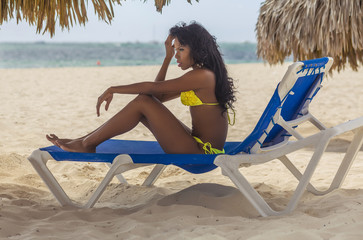 pretty black girl in yellow bikini resting on the  beach