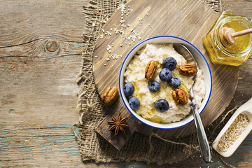 Healthy breakfast: milk porridge from oat bran on skimmed milk with honey, juicy blueberries, pecans on a simple wooden background with a spoon and a jar of honey. Top View.