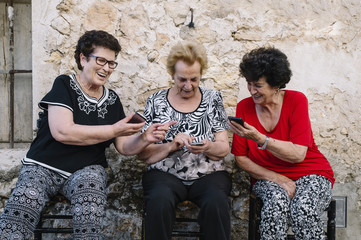 Three women of age advanced with smartphone