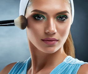 Front view of attractive, sensual woman have bronze clean skin, with bandage on head, drawing blush for herself. Girl holding cosmetic ankle, making professional makeup, looking at camera. Studio.