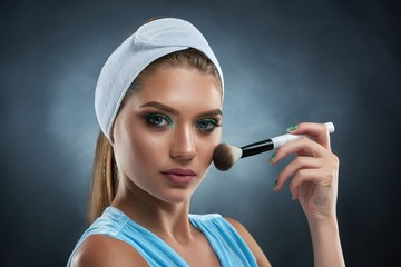 Portrait of gorgeous woman wearing in blue with bandage on head, holding in hand ankle and drawing blush for herself. Brunette girl making professional makeup, posing at camera. Concept of beauty