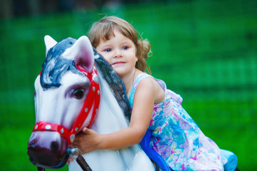 Cute little girl having fun outdoors in the summer park and riding a toy horse