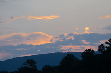 The predawn sun illuminates the clouds over the hills near Anniston, Alabama, USA