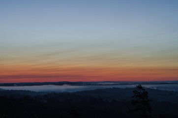 Distant lights and fog near the horizon just before sunrise near Heflin, Alabama, USA