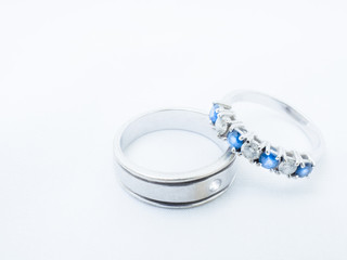 white diamond and blue gemstones on white gold wedding rings with white background and copy space