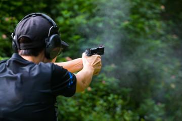 Gun in girl's hands on shooting range
