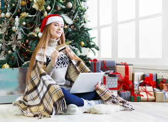 Young woman shopping online in cozy christmas interior