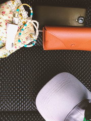 traveler's accessories on the black seat , black sunglasses , case and phone with copy space background