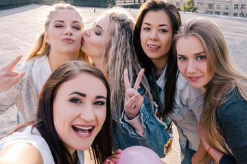 Modern social communication. Female friendship. Happy girls taking selfie on street point of view