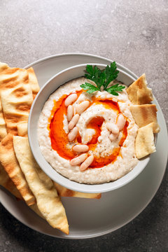 Hummus of white beans with spicy oil of hot pepper and homemade crispy loaves on a gray stone table