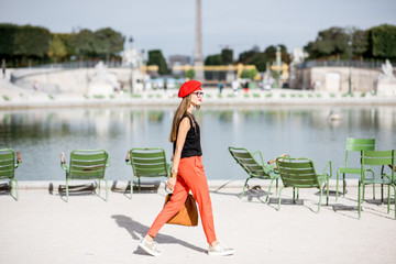 Young woman in red walking in Tuileries park in Paris Wall mural
