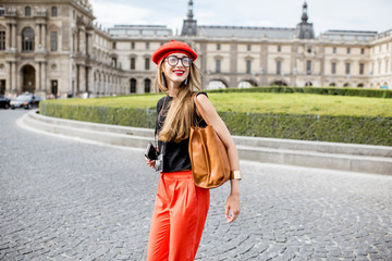 Young woman tourist in red cap walking with photo camera near the famous Louvre museum in Paris