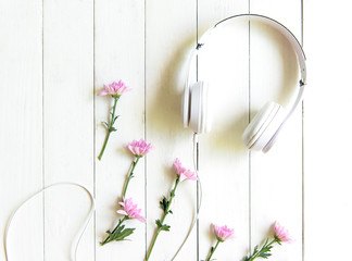 Top view headphones on white desk with pink flower and copyspace area for a text. Music and lifestyle Concept