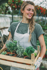 Portrait of a beautiful woman holding plants in the greenhouse