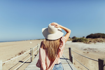 woman with hat  standing idle of the  wooden bridge