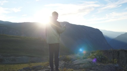 Tourist man making photos with smart phone on peak of rock in the mountains with lens flare effects.