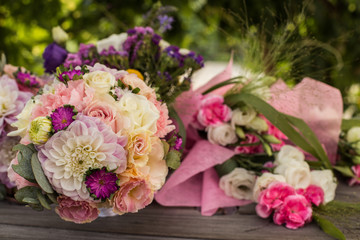 Wedding bouquet with pink, white and violet flowers - set on a wooden table.