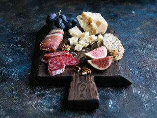 Dark board with various meat, cheese, grapes, bread and figs on a dark background