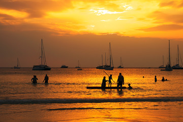 Silhouettes of group of people in ocean at sunset, Nai Harn beach, Phuket, Thailand.