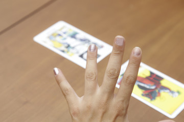 Fortune teller using tarot cards on wooden table