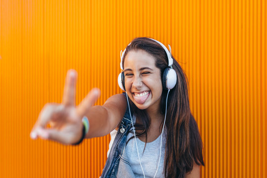 Happy Teen Girl with Headphones Doing the Victory Sign and Stick