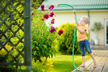 Cute little girl watering flowers in the garden at summer day.