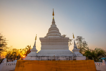 Wat Phra That Khao Noi in Nan, north of Thailand at sunrise sky. The sacred stupa containing Buddha's relics enclosed with pagoda blanket.