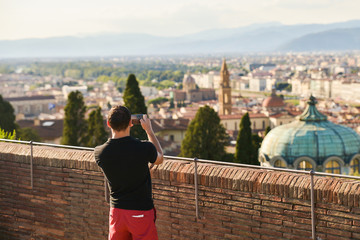 Man taking a mobile photo of Firenze, Italy