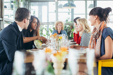 Seven Friends Sitting on Large Table in Bright Modern Restaurant