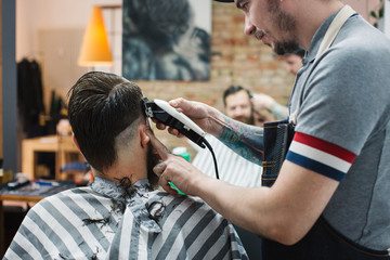 Profile of Young Artisan Barber Cutting Hair With Electric Clipper