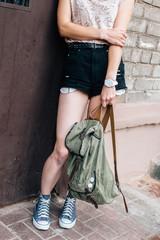 Sad teenage girl posing with backpack on the street near her house door