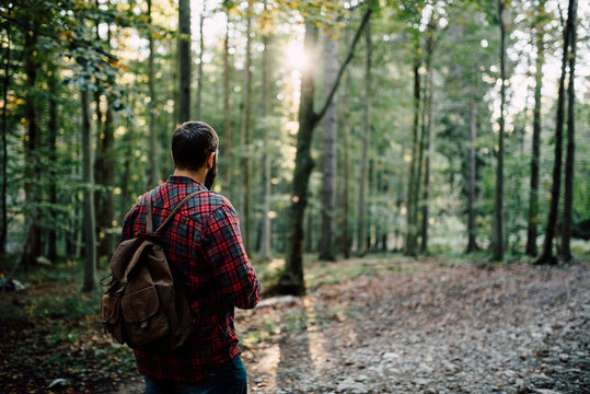 Man in a plaid shirt and backpack in the nature