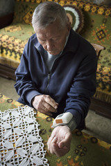 Senior man measuring his blood pressure in his living room