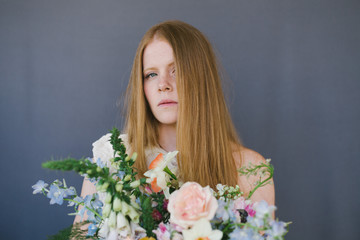 Redheaded Female Holding A Bouquet of Flowers