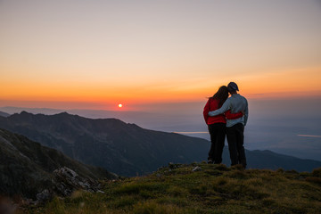 Couple watching sunset over the mountains. Holding each other. Romantic scenery. Friendship.