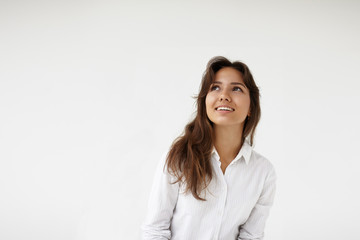 Isolated studio shot of beautiful woman employee wearing white formal shirt looking up and smiling cheerfully, daydreaming, planning holidays during break at office with blank copy space wall